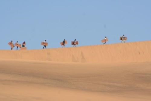 sandboarder climbing the dunes