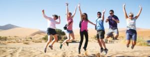 people jumping in namibian desert