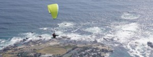 Paraglider glides along the coast